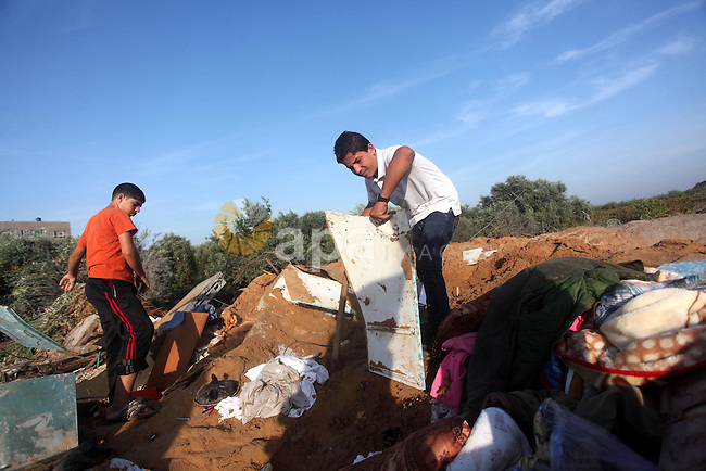 "Palestinians inspect the damage after an Israeli retaliatory air strike demolished the house of a Palestinian family on October 11, 2015 in the Zeitun sector south of Gaza City. A pregnant Palestinian mother and her toddler daughter were killed in the air strike while three others were still trapped under the home's ruins, medical sources said. Israel said it had targeted ""two Hamas weapon manufacturing facilities"" in response to two rocket launches at Israel the day before. Photo by Ashraf Amra"