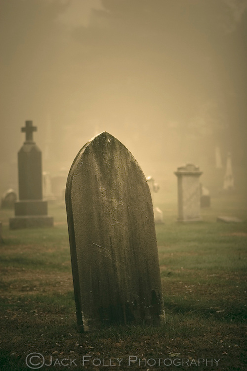 Very old and worn grave stone on a foggy morning.