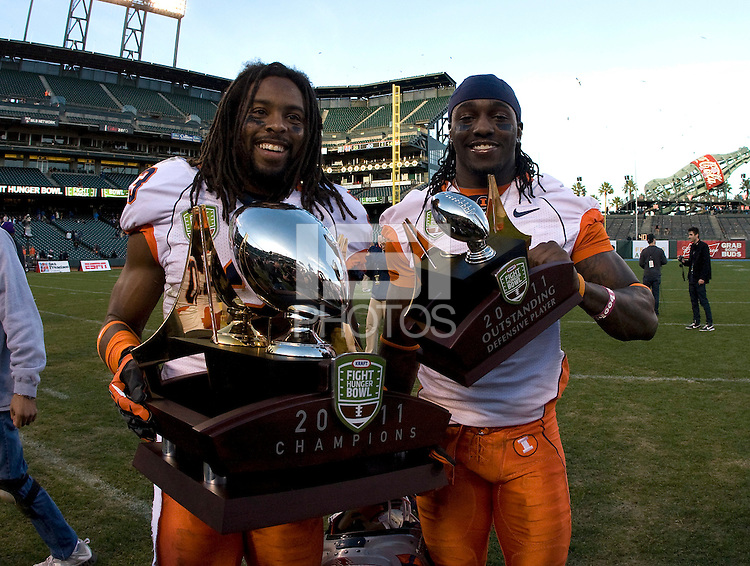 Ben Mathis of Illinois holds Kraft Bowl Trophy and Terry Hawthorne holds Outstanding Defensive Player trophy after winning Kraft Bowl against UCLA at AT&T Park in San Francisco, California on December 31st, 2011.   Illinois defeated UCLA, 20-14.