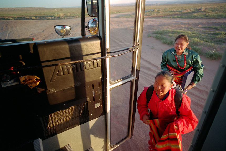 Two traditionally-dressed Navajo girls climb aboard William Mustache's school bus on a remote route south of Blanding, Utah. Mustache drives a bus for the San Juan School District in southeastern Utah, which includes a strip of the vast Navajo reservation. Trips on his bus are some of the longest in the coutry, at an hour and 45 minutes each way for some of his riders. (Photo/Kevin Moloney for the New York Times)