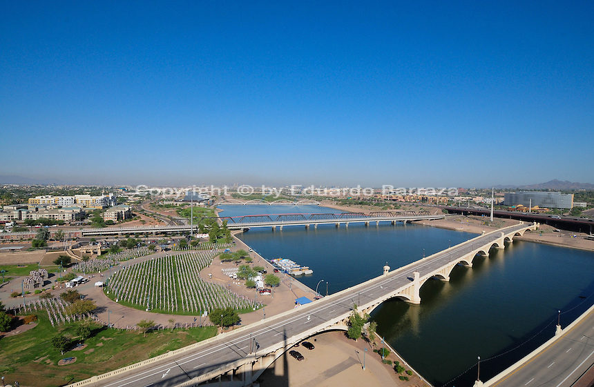 Tempe, Arizona. An aerial western view of Tempe Town Lake showing four of its bridges: the Mill Avenue bridges (right bottom); the Light Rail bridge (center); and, the pedestrian bridge (whit white archs just above light rail bridge). The Tempe Beach Park is seen on the left. Photo By Eduardo Barraza © 2019