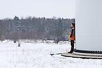 Mirosława Horodiuk rests against a wind turbine on his farm.