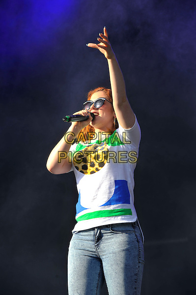 Katy B (Kathleen Anne Brien).performing at 'As One In The Park' festival, Victoria Park, London, England. 26th May 2013.on stage in concert live gig performance music half length singing white top sunglasses shades blue green leopard print jeans denim hand arm in air.CAP/MAR.© Martin Harris/Capital Pictures.
