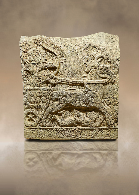 Photo of Hittite relief sculpted orthostat stone panel of Long Wall Basalt, Karkamıs, (Kargamıs), Carchemish (Karkemish), 900 - 700 BC. Anatolian Civilizations Museum, Ankara, Turkey.<br /> <br /> Chariot. One of the two figures in the chariot holds the horse's headstall while the other throws arrows. There is a naked enemy with an arrow in his hip lying face down under the horse's feet. It is thought that this figure is depicted smaller than the other figures since it is an enemy soldier. The tower part of the orthostat is decorated with braiding motifs.<br /> <br /> On a brown art background.