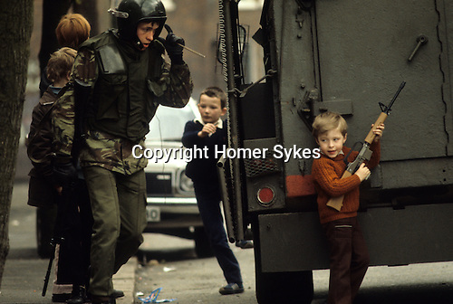 Kids playing with guns,armed British soldier during The Troubles Belfast Northern Ireland 1981.