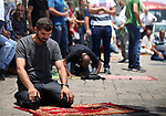 Palestinians pray outside the Lion's Gate  main entrance to the Al-Aqsa mosque compound in Jerusalem's Old City on July 24, 2017 as Palestinians protest against Israel's newly-installed security measures at the entrance to the al-Aqsa mosque compound. Photo by Amir Abed Rabbo