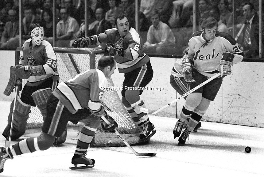 Seal's Tom Williams battles with Pittsburg Penguin Dunc McCallum and Val Fonteyne, goalie is Al Smith..    (1971 photo/Ron Riesterer)