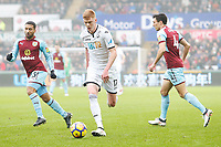 Sam Clucas of Swansea City is chased by Aaron Lennon of Burnley during the Premier League match between Swansea City and Burnley at the Liberty Stadium, Swansea, Wales, UK. Saturday 10 February 2018