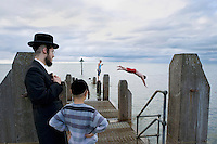 An Hasidic father and son watch locals go for an afternoon swim off a pier in Aberystwyth.
