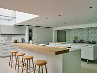 A chunky wooden worktop is used as a breakfast bar on the central island in the kitchen dining area