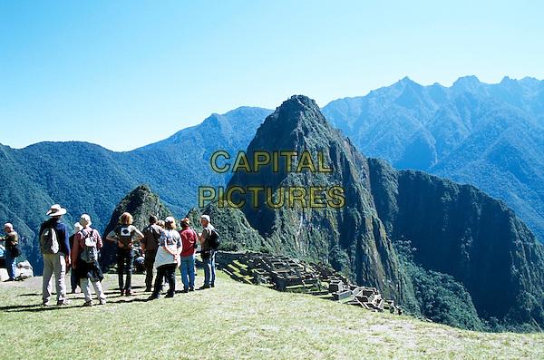 Machu Picchu Inca ruins, visitors on hilltop and Huayna Picchu, Peru