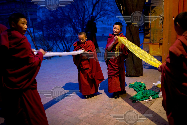 Child Tibetan monks fold khata, sacred scarves, at Rongwo monastery (Longwu in Chinese) in Rebkong (Tongren in Chinese).