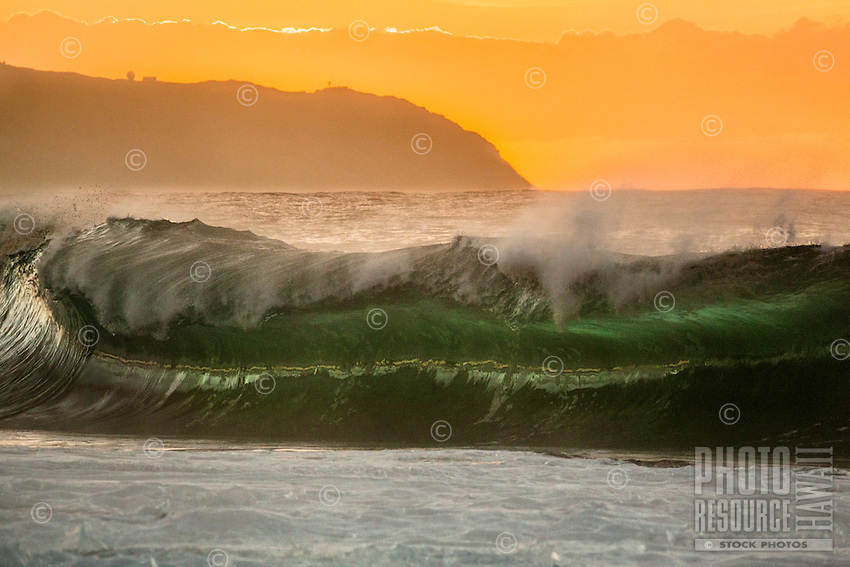 A glowing green breaking wave backed by an orange sky above Ka'ena Point during sunset, seen from Ke'iki Beach, North Shore, O'ahu.