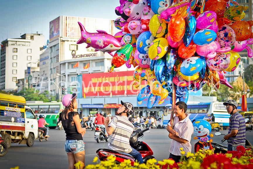 VIETNAM, Ho Chi Minh, Saigon, young woman getting a baloon from a street vendor, motorcycles in the back