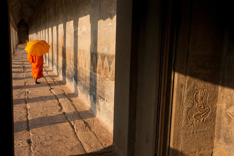 Monk walking among the columns of the gallery at Angkor Wat.