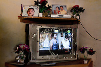 """Photographs of Shardaben's pregnancy (right) and 2nd surrogacy baby are displayed atop the television set in her living room...Shardaben Kantiben, 31; Husband is Kantibhai Motibhai (37).3 children --- 2 girls -  Usha(15) and Lakshmi (18, in pink); 1 boy, Chintan (17).- Education costs for all three come to Rs. 15,000 per year.- Shardaben was a two-time surrogate. First time she gave birth to twin girls for a Taiwanese couple and the second time a boy for an Indian couple from America (photo on TV set because she's proud that it was a boy).- The second time she became emotional and they got a gold ring of Rs. 1,500 made for the boy, which they presented to the biological parents. They are not in touch with either couple..- From the two surrogacies, they earned a little over 700,000rupees..-200,000rupees will be given as dowry for Lakshmi's wedding..- They leased agricultural land (Rs. 2 lakhs for five years) which earns them Rs. 60,000-70,000 a year; they bought two buffaloes worth Rs. 60,000 and make almost 6000-7000 per month selling milk; they bought a motorbike for Rs. 25,000; they put some money into house repairs and the construction of toilets, and opened a fixed deposit in Shardaben's name for Rs. 1.5 lakh and one in the name of their son, Chintan, for Rs. 25,000..Quotes..""""Everyone says they'll keep in touch and take down addresses and phone numbers but nobody looks back. And I guess it works well. Our main interest was in the money. Their main interest is in the baby."""" - KantiBhai.""""Their rules apply at the surrogate house. It does curtail the freedom. When I used to go, everybody would just be lying. They count the days when they can go back."""" - Kantibhai.""""Ours is natural birth but surrogacy is a man-made pregnancy. There's a lot of risk. She must have taken at least 300 injections."""" - Kantibhai of his wife...The Akanksha Infertility Clinic is known internationally for its surrogacy program and currently has over a hundred surrogate mothers pregnant in their"""