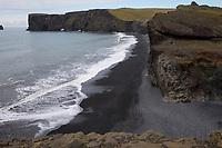 """Kap Dyrhólaey, Dyrholaey, """"Türlochinsel"""" ist eine 115 m hoch aufragende Halbinsel im Süden Islands, etwa 6 km westlich von Vík í Mýrdal, mit Strand Reynisfjara im Vordergrund, dem berühmten schwarzen Sandstrand, Island."""