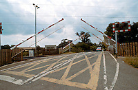 Approach to a railway level crossing. The lights are red and the barriers are dropping down to ensure that no vehicles cross the tracks in front of the train.
