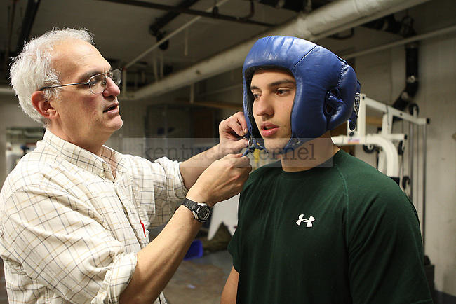 Sigma Alpha Epsilon sophomore Tanner Spangler is assisted by volunteer boxing coach Dr. Larry Herman as he straps on his helmet at Alumni Gym in Lexington, Ky., on Tuesday, November 5, 2013.The Main Event that will be held November 7th and 8th at Lexington Convention Center. Photo by Michael Reaves | Staff