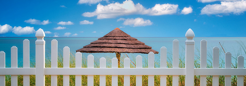 Fence and beach umbrella. Turks and Caicos. Providenciales