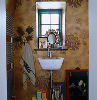 Gold floral wallpaper covers the walls of the small bathroom