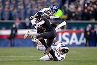 PHILADELPHIA, PA - DEC 8, 2018: Army Black Knights running back Malik Hancock (16) breaks the tackles of Navy Midshipmen defensive end Jarvis Polu (90) and Navy Midshipmen safety Juan Hailey (13) to pick up a first down during game between Army and Navy at Lincoln Financial Field in Philadelphia, PA. Army defeated Navy 17-10 to win the Commander in Chief Cup. (Photo by Phil Peters/Media Images International)