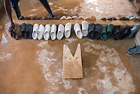 A wooden device used to take off rubber boots without touching them sits near a row of sandals in the decontamination area. Occidental College professor Mary Beth Heffernan works on her PPE Portrait Project with health care workers at the ELWA II ETU (Ebola treatment unit) in Monrovia, Liberia on Saturday, March 8, 2015. <br /> (Photo by Marc Campos, Occidental College Photographer) Mary Beth Heffernan, professor of art and art history at Occidental College, works in Monrovia the capital of Liberia, Africa in 2015. Professor Heffernan was there to work on her PPE (personal protective equipment) Portrait Project, which helps health care workers and patients fighting the Ebola virus disease in West Africa.<br />
