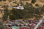 September 20, 2004 Angels Camp, California --Tuolumne Fire –- CDF helicopter 404 arrives at Frog Town, Calaveras County Fairgrounds, for fallen firefighter Eva Marie Schicke's memorial service. The Tuolumne Fire was a small very fast-moving fire that started around noon on September 12, 2004 near Lumsden Bridge at the bottom of the Tuolumne River.  The fire moved rapidly up the 80-plus-degree slope catching Cal Fire Helitack firefighters, tragically killing firefighter Eva Marie Schicke and injuring five others.