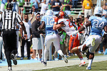 19 September 2015: UNC's Marquise Williams (12) is knocked out of bounds by Illinois' Eaton Spence (27). The University of North Carolina Tar Heels hosted the University of Illinois Fighting Illini at Kenan Memorial Stadium in Chapel Hill, North Carolina in a 2015 NCAA Division I College Football game. UNC won the game 48-14.