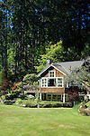 A wood-shingled waterfront weekend vacation retreat sits amid towering evergreen trees on Washington State's Vashon Island.  The small sitting gazebo can just be seen on the slope above the house on the left edge.