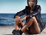 Young woman in black leather jacket sitting at the beach