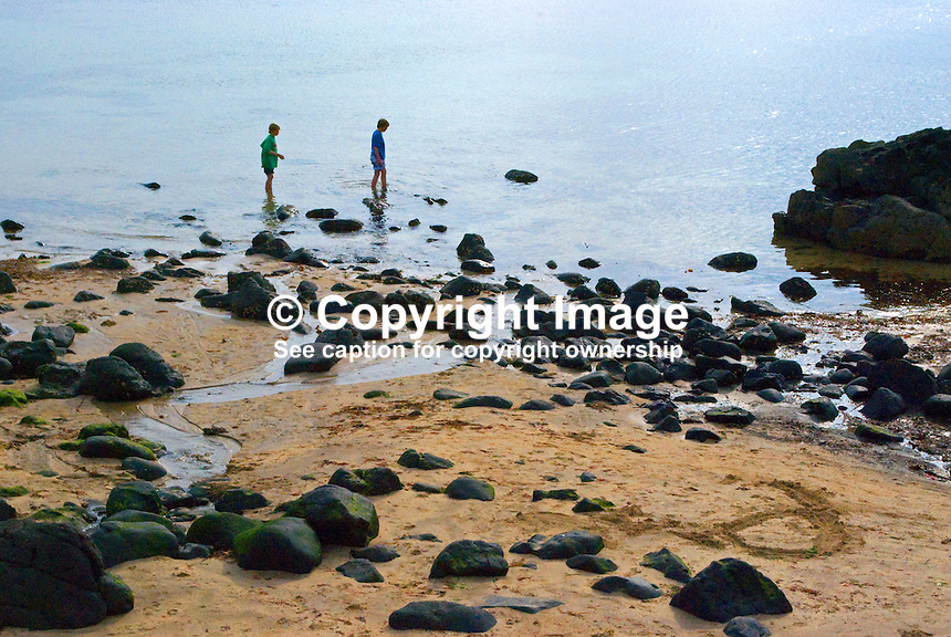 Beach, rocks, sand, sea, paddlers, young, boys, Portstewart, Co Londonderry, N Ireland, UK, 200906292774..Copyright Image from Victor Patterson, 54 Dorchester Park, Belfast, UK, BT9 6RJ..Tel: +44 28 9066 1296.Mob: +44 7802 353836.Voicemail +44 20 8816 7153.Skype: victorpattersonbelfast.Email: victorpatterson@mac.com.Email: victorpatterson@ireland.com (back-up)..IMPORTANT: If you wish to use this image or any other of my images please go to www.victorpatterson.com and click on the Terms & Conditions. Then contact me by email or phone with the reference number(s) of the image(s) concerned.