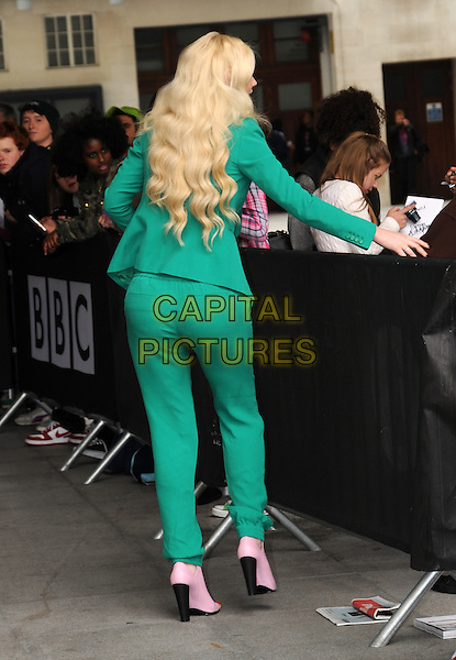 Iggy Azalea<br /> At BBC Radio 1, London, England.<br /> May 31st, 2013<br /> full length green suit print pink fans crowd signing autographs back behind rear boots<br /> CAP/AOU<br /> &copy;AOU/Capital Pictures
