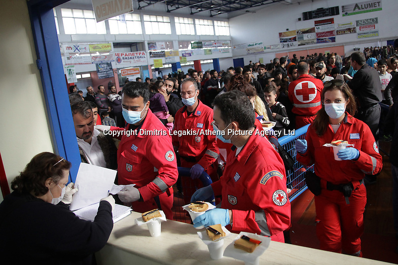 Pictured: red Cross personnel assist with the hundreds of migrants in Ierapetra basketball arena. Friday 28 November 2014<br /> Re: 700 migrants aboard a ship that lost power in the Mediterranean Sea with and was towed into a Greek harbor are being housed in a basketball arena while their refugee status was assessed.<br /> It took the Greek navy four days to tow the ship Baris from international waters into Ierapetra harbor, on the Greek island of Crete. The vessel lost power in storm-force winds.<br /> Many are Syrians fleeing the civil war. A senior health official on the island, Panayiotis Efstathiou, said many would be released.