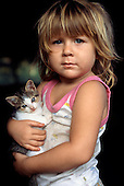 Osa Peninsula, Costa Rica. Milagro, a blonde girl, holding a kitten.