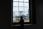 A young boy looks out a window at a windmill being used to generate power at the Tetra Foods plant from inside The Plant in The Back of the Yards neighborhood in Chicago, Illinois on December 21, 2014.  The Plant is a four-year old facility that has taken over a former pork processing plant in an effort to convert the facility to an indoor vertical farm, very much still under construction, run on the biomass fuel provided by a waste-processing anaerobic digester.