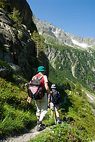 CHE, SCHWEIZ, Kanton Bern, Berner Oberland, Paar beim Wandern mit Rucksack und Wanderstoecken | CHE, Switzerland, Bern Canton, Bernese Oberland, couple hiking