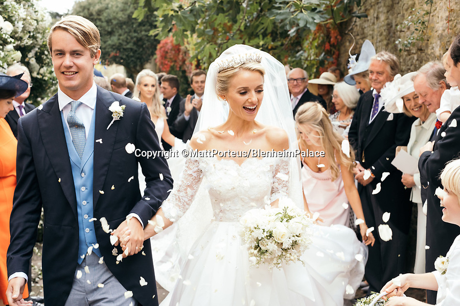 BNPS.co.uk (01202 558833)<br /> Pic: BlenheimPalace<br /> <br /> Lord and Lady Blandford's lavish wedding at Blenheim last year.<br /> <br /> The stunning wedding dress worn by Camilla Thorp on her marriage to Lord George Blandford, heir to the Duke of Marlborough, has just gone on display at Blenheim Palace in Oxfordshire.<br /> <br /> The first bespoke Dolce & Gabbana bridal gown ever to have been worn in Britain, Lady Blandford made several visits to the Milan fashion house prior to her lavish September wedding last year.<br /> <br /> The dress, which is on display in the Palace's Long Library, features an off-the-shoulder lace bodice with tiny, pale pink and white appliqued flowers and seed pearls. <br /><br />The skirt is made up of layers of tulle for volume and topped with organza. Lace is also featured on the hem of the skirt and around the edge of the silk tulle veil.