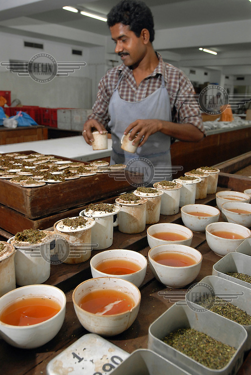 A worker clears away cups after a tasting session in the tea tasting rooms at an auction house.