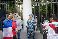 MOSCOW, RUSSIA - June 14, 2018: A Russia military officer attempts to stop fans from jumping or squeezing through the fence outside Moscow State University attempting to enter the Moscow FIFA Fan Fest during the opening match of the 2018 FIFA World Cup. The Fan Fest was closed by officials because it was at capacity.