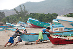 fishermen pull their boat on the beach in puerto lopez ecuador
