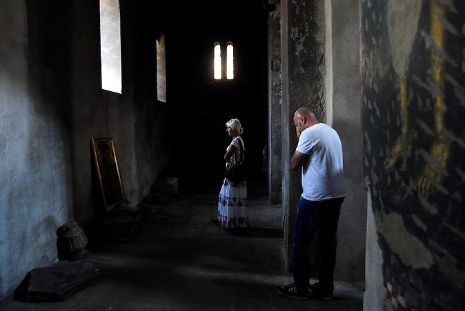 Betende in einer stark beschädigten Kirche im Zentrum von Prizren / Serbische Reisegruppe in serbischen Enklaven im Kosovo, mitorganisiert von Branka Krneta, einer25-jährigen Serbin. Sie fahren an historisch serbisch dominierte Orte. Die Teilnehmer stehen meist der nationalistischen Organisation Kosmet nahe und sehen Kosovo als Teil Serbiens.