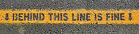 'Behind this line is fine' notice painted next to the edge of the platform at an inner Brisbane suburban train station.