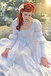 A sad-looking young woman with flowers in her red hair wearing a wedding dress sitting longingly in front of a pond with sunlight