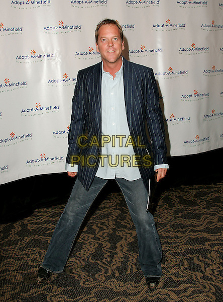 KIEFER SUTHERLAND.The 4th Annual Benefit Gala for Adopt-A-Minefield held at The Century Plaza Hotel in Century City, California.October 15th, 2004.full length, jeans, denim, pinstripe jacket, legs spread.www.capitalpictures.com.sales@capitalpictures.com.©Debbie Van Story/Capital Pictures