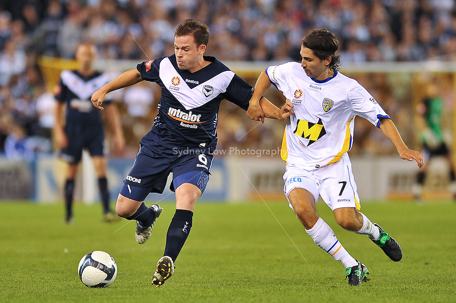 MELBOURNE, AUSTRALIA - NOVEMBER 28, 2009: Leigh Broxham from Melbourne Victory fights for the ball with  Zenon Caravella in round 16 of the A-league match between Melbourne Victory and Gold Coast United at Etihad Stadium on November 28, 2009 in Melbourne, Australia. Photo Sydney Low www.syd-low.com