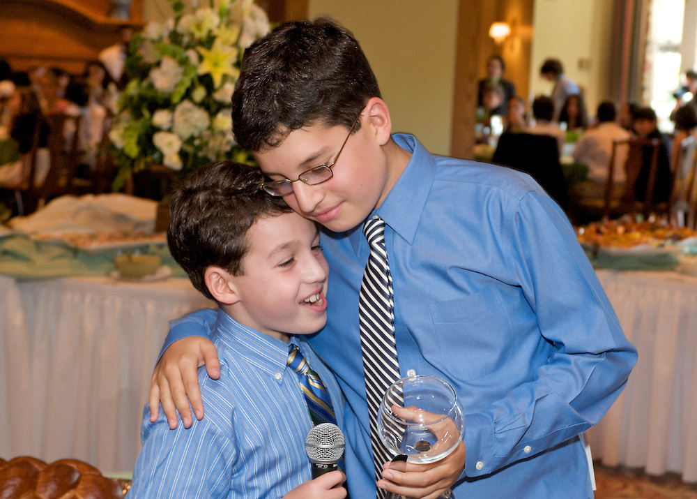 Bar Mitzvah boy embracing his brother after the toast.