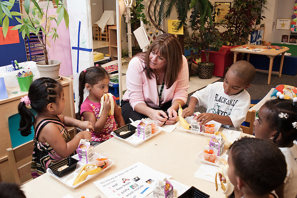 September 14, 2011. Raleigh, NC. . Susan Swearingen, the teaching assistant, helps the children with their lunches.. Project Enlightenment, a public pre-kindergarten program for at risk children, has been threatened with closure due to state wide budget cuts..