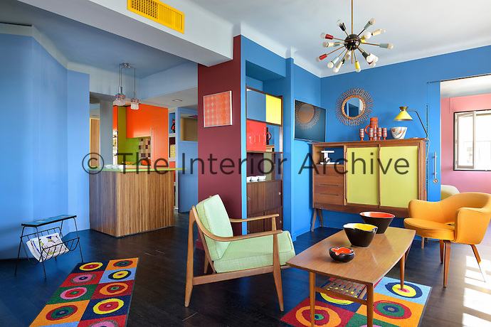 This colourful living room with open plan kitchen area is furnished with vintage pieces