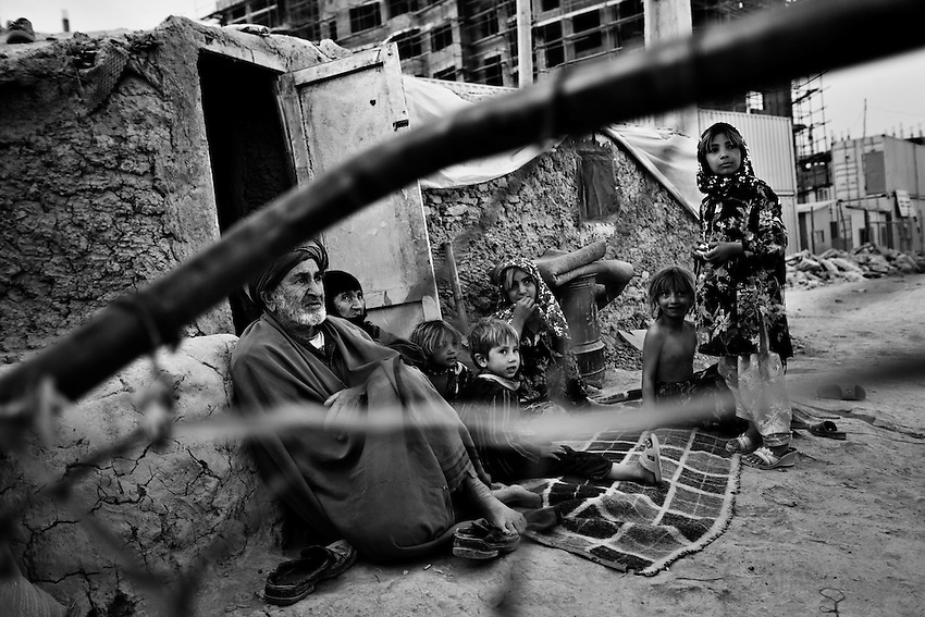 A displaced Afghan family sits at the front of a mud house in Chamane Babrak, a tented slum community for displaced Afghans just west of Kabul, Afghanistan, Monday, Oct 5, 2009. The majority of the familes in Chamane Babrak are returnees from Iran.